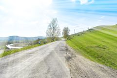 Schöne Asphaltstraße auf dem großen grünen Hügel an einem sonnigen Sommertag lizenzfreie stockfotos