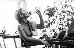 Schöne athletische blonde Frau ist Trinkwasser auf einer Tretmühle in der Turnhalle Lizenzfreies Stockfoto