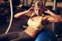 Schöne athletische Frau, die AB-Abstände in der Eignung Arbeits ist Stockfotos