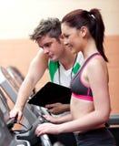 Schöne athletische Frau, die auf einem treadmilll steht lizenzfreie stockbilder