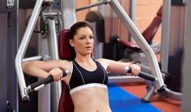 Schöne athletische Frau, die eine Bankpresse verwendet lizenzfreie stockfotografie