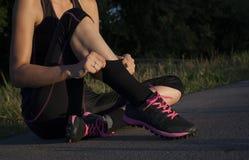 Schöne athletische junge erwachsene Frau wird fertig, Übungen zu tun und zieht Socken hoch lizenzfreie stockfotografie