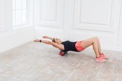 Schöne athletische junge Frau in der modernen geeigneten Abnutzung unter Verwendung der Schaumrolle in der Turnhalle zum Training lizenzfreies stockbild