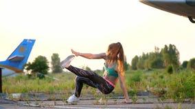 Schöne, athletische, junge Frau in der Sonnenbrille, in den Strumpfhosen, führt verschiedene Stärkeübungen, Sprünge, StoßUPS durc stock video footage