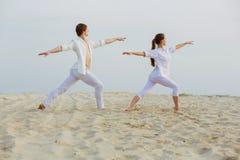 Schöne, athletische Paare in der weißen Kleidung, die Yoga exercis macht Lizenzfreie Stockbilder
