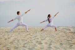 Schöne, athletische Paare in der weißen Kleidung, die Yoga exercis macht Lizenzfreies Stockbild