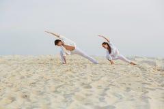 Schöne, athletische Paare in der weißen Kleidung, die Yoga exercis macht Stockfotos