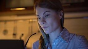 Schöne attraktive überarbeitete betonte Geschäftsfrau, die an Laptop arbeitet Abend-Nachtküche stock video
