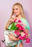 Schöne attraktive blonde junge Frau mit afrikanischen Borten mit Tulpen auf rosa Hintergrund Stockbilder