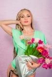 Schöne attraktive blonde junge Frau mit afrikanischen Borten mit Tulpen auf rosa Hintergrund Lizenzfreies Stockbild