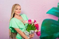 Schöne attraktive blonde junge Frau mit afrikanischen Borten mit Tulpen auf rosa Hintergrund Lizenzfreie Stockfotos