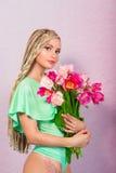 Schöne attraktive blonde junge Frau mit afrikanischen Borten mit Tulpen auf rosa Hintergrund Stockfoto