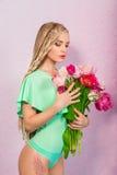 Schöne attraktive blonde junge Frau mit afrikanischen Borten mit Tulpen auf rosa Hintergrund Lizenzfreies Stockfoto