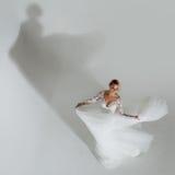 Schöne attraktive Braut im Hochzeitskleid mit langem Tellerrock, weißem Hintergrund, Tanz und Lächeln, Draufsicht Stockfoto