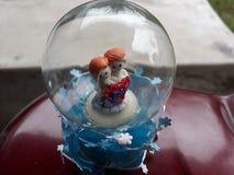 Schöne attraktive dekorative Glaskugel mit reizenden Paaren stockfoto