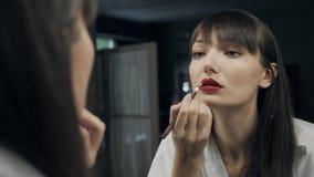 Schöne attraktive Frau bilden selbst vor dem Spiegel, zum photoshot fertig zu werden und ihr Auge zur Kamera zu blinzeln Lizenzfreie Stockfotos