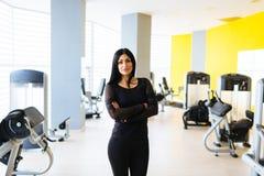 Schöne, attraktive Frau - Eignungstrainer auf dem Turnhallenhintergrund Übungskonzept Kopieren Sie Platz stockbild