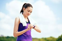 Schöne attraktive Frau machend im Freien vor oder nach Training und Betrieb im Park, ihre Laufzeit überprüfend stockbild