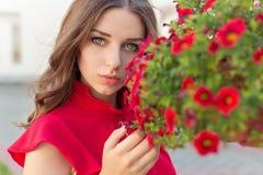 Schöne attraktive Frau mit dem langen Haar in einem roten Kleid nahe dem Rot blüht im Garten Lizenzfreie Stockfotografie