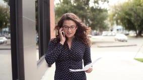 Schöne attraktive Geschäftsfrau hebt Dokumente auf, nachdem sie die guten Nachrichten gehört hat stock footage