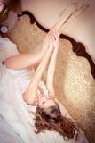 Schöne attraktive junge blonde sexy Frau, die in den Bettarmen und -beinen aufgestellt mit Wecker auf dem Hintergrund sich entspa Lizenzfreies Stockbild