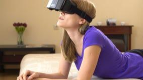 Schöne attraktive junge Frau, die auf Sofa unter Verwendung der Gläser der virtuellen Realität liegt stock video