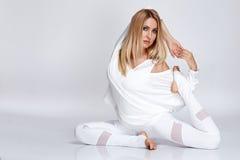 Schöne attraktive sexy blonde Frau, die das Yoga herein sitzt tut Lizenzfreie Stockfotografie