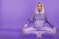 Schöne attraktive sexy blonde Frau, die das Yoga herein sitzt tut Stockbilder
