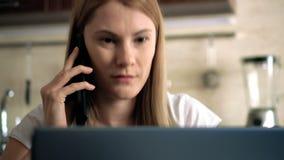 Schöne attraktive zufällige junge Frau, die in einer Küche sitzt und am Telefon mit einem Freund spricht stock video footage