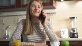 Schöne attraktive zufällige junge Frau, die in einer Küche sitzt und am Telefon mit einem Freund spricht stock footage