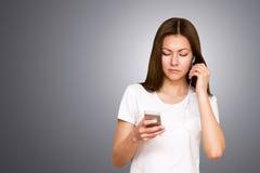 Schöne attraktive zufällige junge Frau, die an ihrem Handy spricht Studio geschossen über grauem Hintergrund stockfotografie