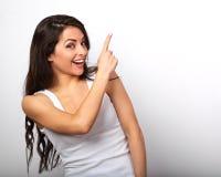 Schöne aufgeregte zufällige Frau, die oben den Finger mit dem Zahn zeigt lizenzfreies stockfoto