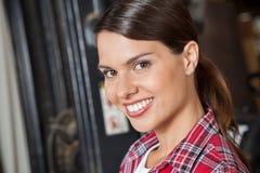 Schöne Aufsichtskraft, die in der Werkstatt lächelt Lizenzfreie Stockfotos