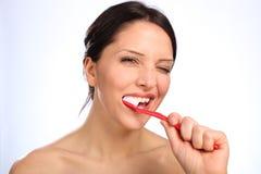 Schöne auftragende Zähne der jungen Frau des Zahnpflegen Stockfotografie