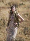 Schöne böhmische Brunettefrau, die auf einem Gebiet des Grases steht Lizenzfreie Stockfotos