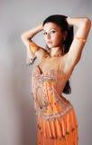 Schöne Bauchtänzerin im orange Kleid Lizenzfreie Stockfotos