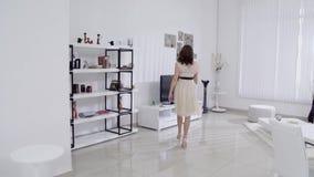 Schöne Beine der jungen Frau in den Schuhen und beige Kleiderbewegungen im Innenraum im Wohnzimmer in der Zeitlupe Reizvolle Fahr stock footage