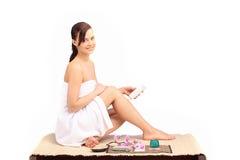Schöne Beine des weiblichen Körpers mit kosmetischer Behälterschüssel und -creme Stockfotografie