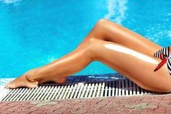 Schöne Beine draußen durch Pool unter Sonnenschein am schönen Sommertag Stockbild