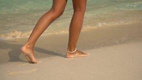 Schöne Beine eines jungen Mädchens, das auf dem Strand wolking ist stock video