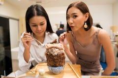 Schöne berufstätige Frauen zwei Schokolade Bingsu essen lizenzfreie stockfotos