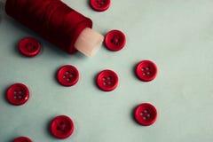 Schöne Beschaffenheit mit vielen runden roten Knöpfen für das Nähen, Näharbeit und eine Spule des Fadens Kopieren Sie Platz Flach stockbild