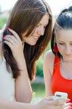 2 schöne beste Freundinnen der jungen Frauen, die den Spaß betrachtet Schirm am weißen Mobilhandy haben Stockbilder