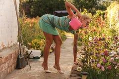 Schöne Bewässerungsblumen des jungen Mädchens auf dem Blumenbeet Das Konzept einer guten Hausfrau in ihrem Haus stockbild