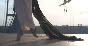 Schöne Bewegung der Beine einer Ballerina, Tänzer, Gymnastik bei Sonnenuntergang stock footage