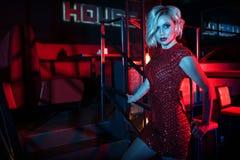 Schöne bezaubernde blonde Frau, die auf der Treppe im Nachtclub in den bunten Neonlichtern steht Stockfotografie