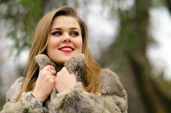 Schöne bezaubernde Dame, die den Spaß im Freien am düsteren Wintertag hat Stockfoto