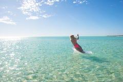 Schöne Bikinifrau, die in tropisches Meer springt Lizenzfreie Stockfotos