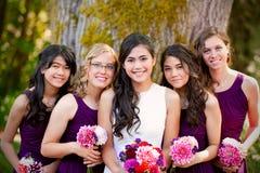 Schöne biracial junge Braut, die mit ihrem multiethnischen grou lächelt Stockfotografie