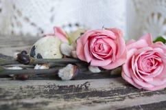 Schöne blühende Rosen blühen, Wachteleier und Weidenniederlassungen auf hölzernem Hintergrund Rote Tulpe und farbige Eier Blumena Lizenzfreie Stockfotografie